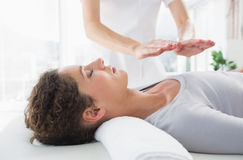 Woman having reiki treatment. Attractive young woman having reiki treatment in health spa Stock Images