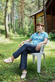 Woman is having rest in a coniferous forest Royalty Free Stock Image