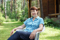 Woman is having rest on the glade in pine forest Stock Images