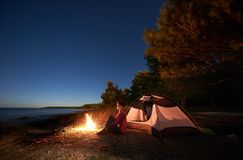 Woman having a rest at night camping near tourist tent, campfire on sea shore under starry sky stock image