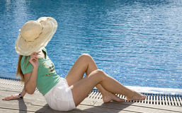 Woman having a rest at pool. Woman smiles having a rest at pool stock image
