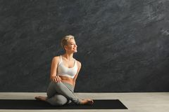 Woman having rest after training yoga in gym. Fitness, happy woman having rest after training yoga in gym at grey background, copy space. Young slim girl makes Royalty Free Stock Photography