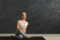 Woman having rest after training yoga in gym. Fitness, woman having rest after training yoga in gym at grey background, copy space. Young slim girl makes Royalty Free Stock Images