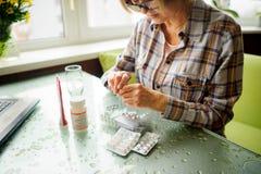 The woman having rheumatoid arthritis takes medicine. Hands are deformed Stock Photography