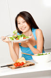 Woman Having Salad. An attractive asian woman having a healthy salad in her kitchen at home stock image