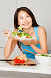 Woman Having Salad. An attractive asian woman having a healthy salad in her kitchen at home stock photography