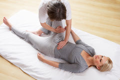 Woman having Shiatsu massage. Lying on the floor royalty free stock photography