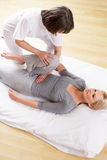 Woman having Shiatsu massage. By professional in her house on exercise mat stock images
