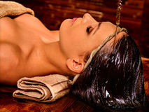 Woman having Shirodhara pouring oil on head in India spa . Royalty Free Stock Images