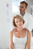 Woman having shoulder massage by chiropractor Stock Photography