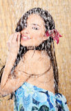 Woman having a shower. Young woman with orchid in her hair having a shower Stock Photography