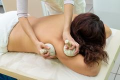 Woman having spa bags massage in wellness salon. Closeup stock photo
