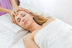 Woman having spa massage of her head. Young beautiful woman having spa massage of her head Stock Image