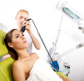 Woman having a stimulating facial treatment from a therapist Stock Photography