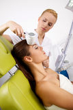 Woman having a stimulating facial treatment from a therapist. Portrait of attractive beautiful young adult brunette women having a stimulating facial treatment Stock Photography
