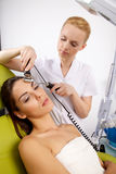 Woman having a stimulating facial treatment from a therapist. Portrait of attractive beautiful young adult brunette women having a stimulating facial treatment Royalty Free Stock Image