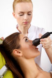 Woman having a stimulating facial treatment from a therapist. Portrait of attractive beautiful young adult brunette women having a stimulating facial treatment Stock Images