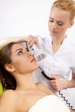 Woman having a stimulating facial treatment from a therapist Royalty Free Stock Image