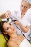 Woman having a stimulating facial treatment from a therapist. Portrait of attractive beautiful young adult brunette women having a stimulating facial treatment Royalty Free Stock Images