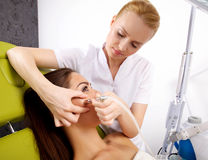 Woman having a stimulating facial treatment from a therapist. Portrait of attractive beautiful young adult brunette women having a stimulating facial treatment Stock Image