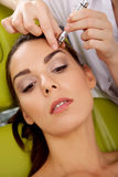 Woman having a stimulating facial treatment from a therapist Royalty Free Stock Images