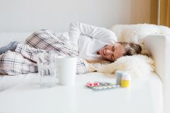 Woman having stomach cramps. While sleeping in bed Stock Photography