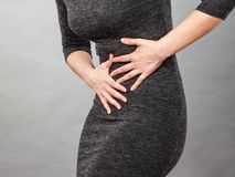 Woman having strong stomach ache. Syndroms. Of indigestion pregnancy. Female suffer on belly pain, holds hands on abdomen, part of body on grey Stock Photography