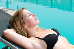 Woman having a sun bath near a swimming pool Stock Photography