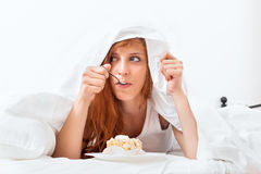 Woman having sweet cake  at bed Royalty Free Stock Photos