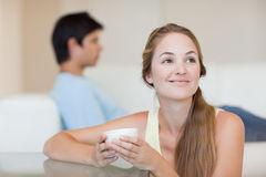 Woman having a tea while her fiance is sitting on a sofa Royalty Free Stock Photo