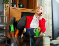 Woman having a tedious time and speaking by mobile. Young woman having a tedious time and speaking by mobile  at office Royalty Free Stock Image