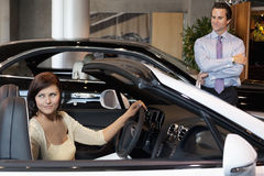 Woman having a test drive while salesperson standing besides car stock photos