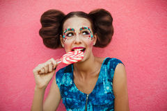 Woman having toothache after eating sweets, lollipop and teeth problem. girl eating sweet candy. caries. Colorful Lollipop in perf Stock Photo