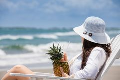 Woman having a tropical drink at a paradisiac tropical beach in a beautiful sunny day. A Woman having a tropical drink at a paradisiac tropical beach in a stock photos