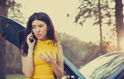 Woman having trouble with her broken car, opening hood and calling for help on cell phone. Green trees and park background royalty free stock image