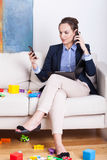 Woman having two phone calls at the same time. Busy woman having two phone calls at the same time royalty free stock image