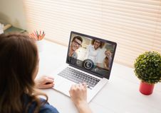 Woman having video call with friends on laptop. At home Stock Image
