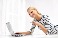 Woman having video call on laptop computer at home. Communication, technology and people concept - smiling young woman having video call and pointing finger to stock images