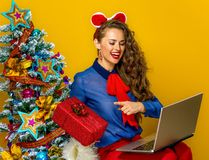 Woman having video chat on laptop and showing present box. Festive season. smiling modern woman near Christmas tree on yellow background having video chat on Stock Photo