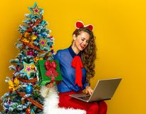 Woman having video chat on laptop and showing present box. Festive season. smiling young woman near Christmas tree on yellow background having video chat on Stock Images