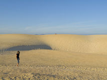 Woman having a walk in the dunes Stock Photo
