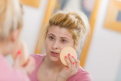 Woman having wash gel on face holding sponge. Complexion, skincare products concept. Woman having wash gel on face holding sponge about to clean her skin Stock Image