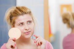 Woman having wash gel on face holding sponge Stock Photo