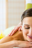 Woman having a wellness back massage. Beautiful woman having a wellness back massage and feeling visibly good about it royalty free stock photos