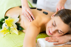 Woman having wellness hot stone massage royalty free stock photos