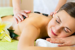 Woman having wellness hot stone massage Royalty Free Stock Photography