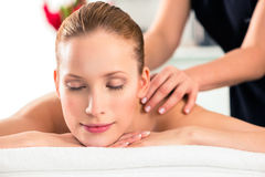 Woman having wellness massage in spa. Woman in wellness beauty spa having back massage with essential oil, looking relaxed stock photography