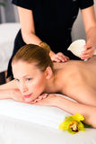 Woman having wellness massage in spa with oil. Woman in wellness beauty spa having back massage with essential oil, looking relaxed stock photo