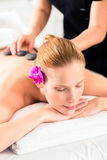 Woman having wellness spa hot stone massage Royalty Free Stock Photos