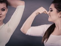 Woman having wet armpit her friend smelling stink Stock Image